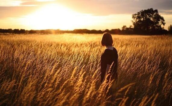 Frau steht bei Sonnenuntergang auf einem Feld