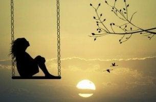 Frau auf einer Schaukel vor der untergehenden Sonne