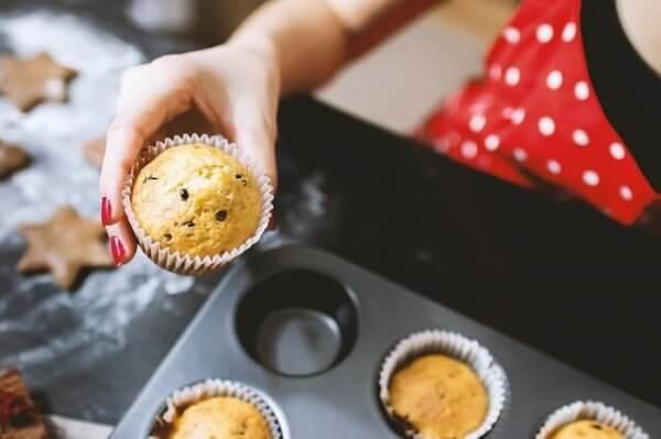 Eine Frau holt einen Muffin aus einer Backform.