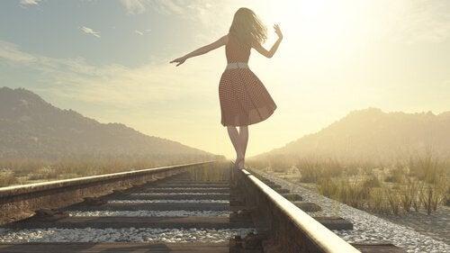 Eine Frau im Kleid balanciert auf einem Bahngleis.