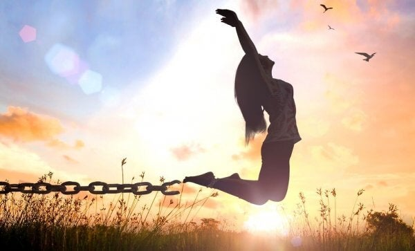 Eine Frau springt und befreit sich aus ihren Ketten.