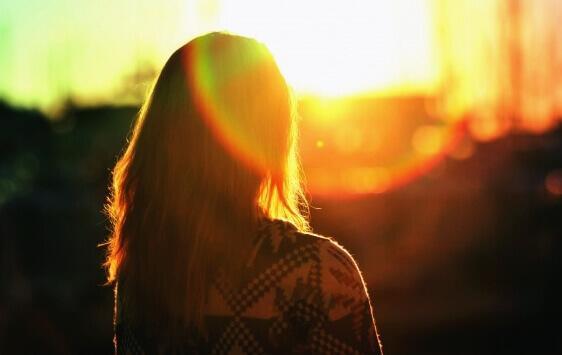 Frau schaut Sonnenaufgang an