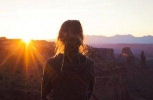 Frau beobachtet den Sonnenuntergang.