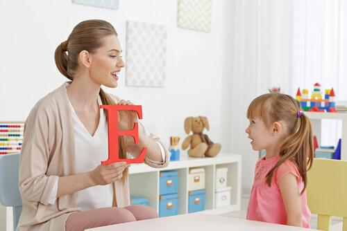 Eine Frau bringt einem Mädchen das Sprechen bei