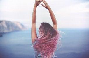 Mehr Spontaneität - Eine Frau blickt auf das Meer und reckt ihre Hände in den Himmel.