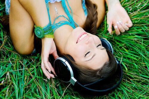 Frau liegt im Gras und hört Musik.