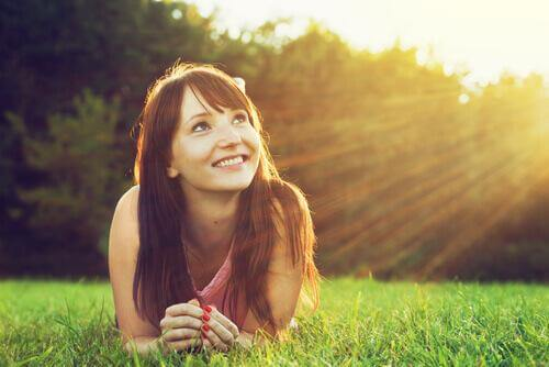 Eine lächelnde Frau liegt im Gras.