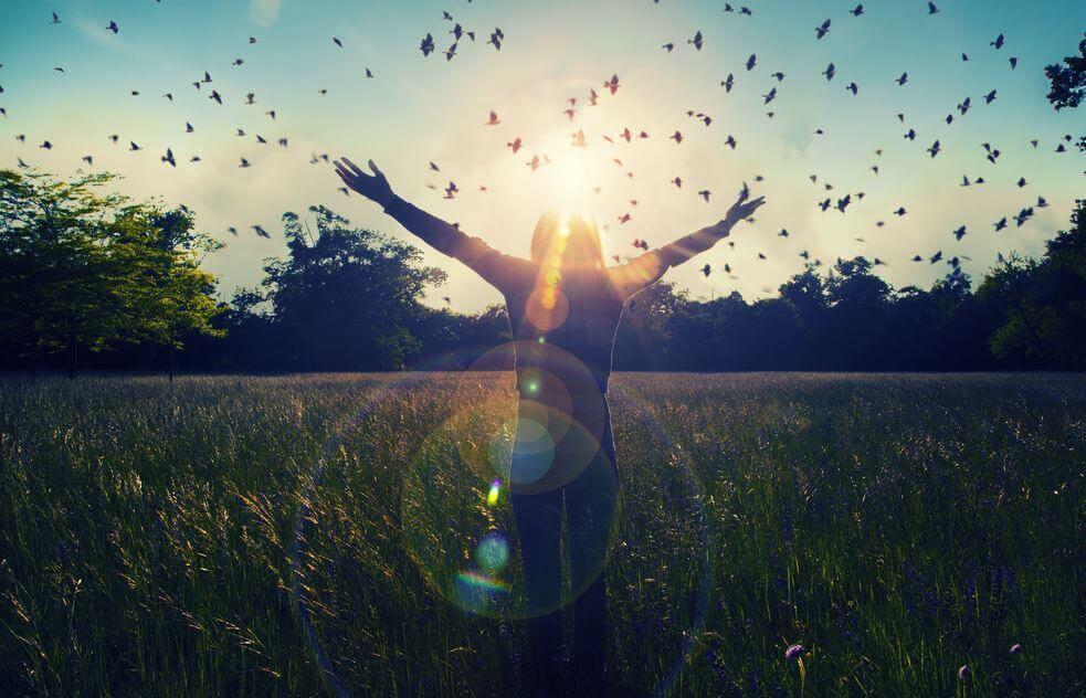 Eine Frau steht in der Natur und reckt ihre Arme in den Himmel, während ein Schwarm Vögel an ihr vorbeizieht.