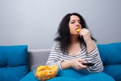 Sitzender Lebensstil - Dicke Frau auf dem Sofa isst Chips