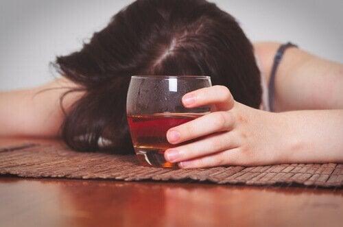 Frau liegt betrunken auf dem Tisch
