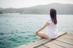 Vorteile von Meditation - Eine Frau sitzt im Lotussitz und meditiert an einem See.