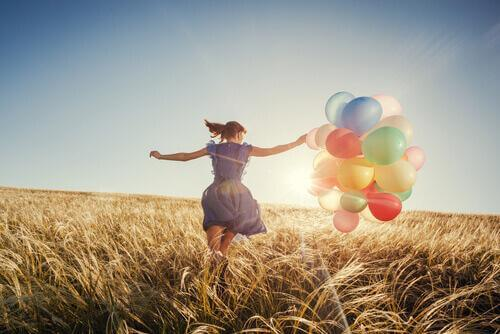 Eine junge Frau läuft mit bunten Ballons über ein Getreidefeld.