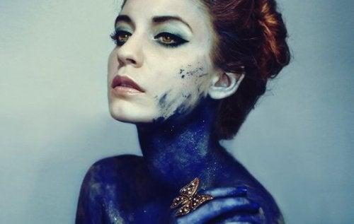 Illusion der Durchschaubarkeit - Frau mit blauer Farbe auf ihrem Körper