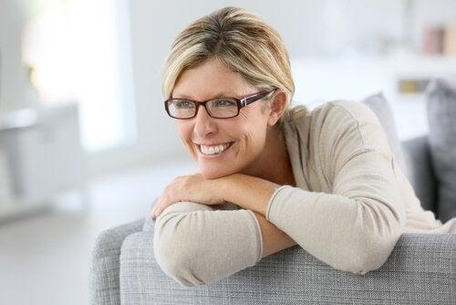 Eine etwas ältere Frau mit Brille lächelt auf der Couch.