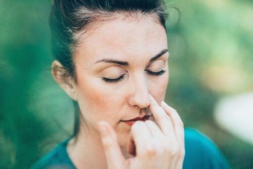 Frau mit geschlossenen Augen praktiziert Wechselatmung