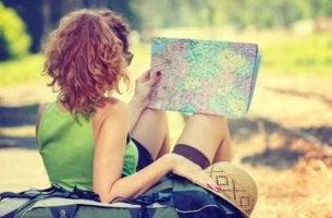 Frau mit Hut schaut auf Landkarte