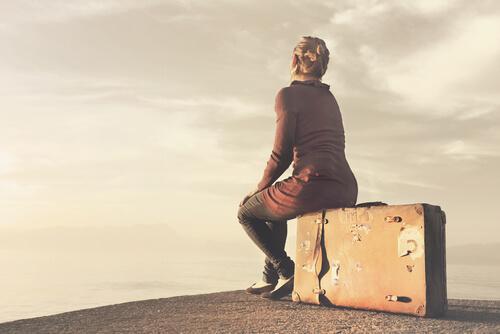Frau sitzt auf einem Koffer