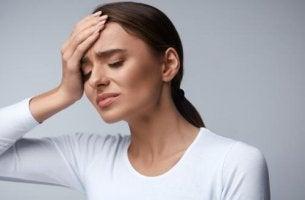 Eine Frau hat Kopfschmerzen durch Dehydratation