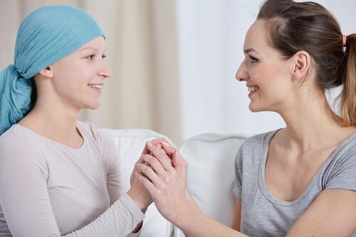 Eine Frau hält die Hand einer an Krebs erkrankten Frau; sie lächeln sich beide an.