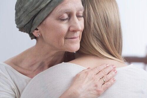 Eine Frau mit Krebs umarmt eine andere Frau.