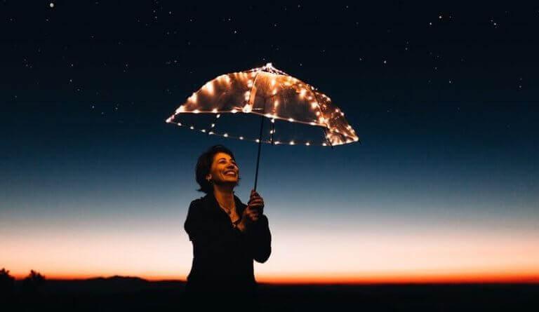Lachende Frau hält einen leuchtenden Schirm