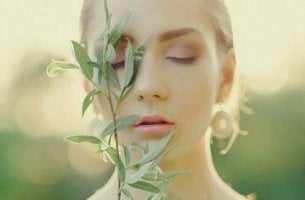 Befremdliche Emotionen - Frau hält sich eine Pflanze ins Gesicht.
