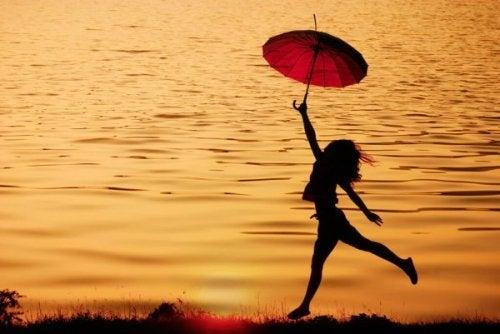 Eine Frau mit einem roten Schirm läuft beschwingt am Wasser entlang.