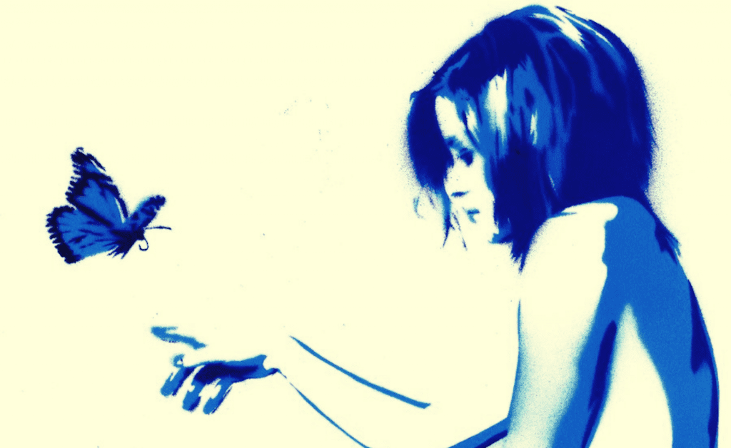 Frau streckt ihre Hand zu einem Schmetterling aus