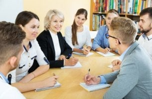 Eine Frau sitzt mit einer Gruppe von Schülern an einem Tisch.