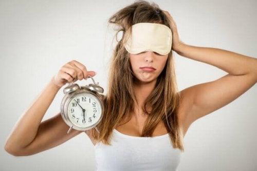 Eine Frau mit Schlafmaske hält einen Wecker in der Hand.