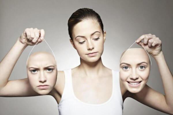 Eine Frau hält zwei Gesichter mit unterschiedlichen Gesichtsausdrücken in den Händen.