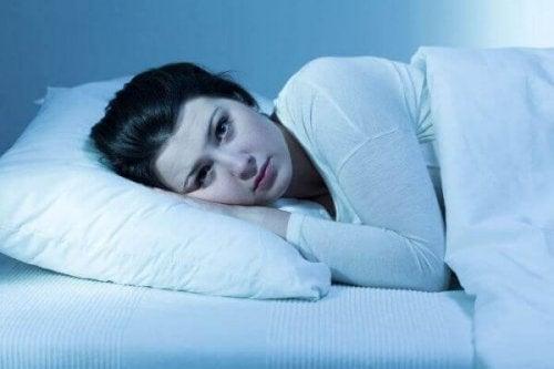 Eine Frau liegt nachts wach im Bett.