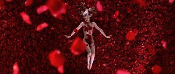 Filmszene aus American Beauty, auf der sich ein nacktes Mädchen auf Rosenblättern rekelt.