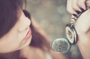 Frau schaut auf eine Taschenuhr