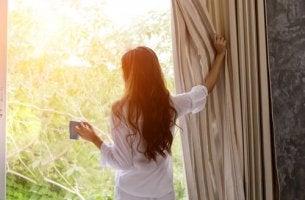 Frau schaut aus dem Fenster als Symbol für frühes Aufstehen