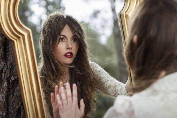 Frau mit Selbstzweifeln schaut in den Spiegel.