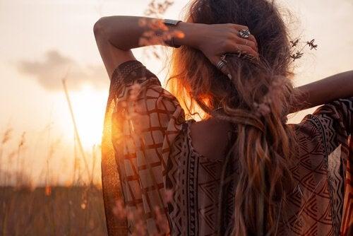 Frau schaut in den Sonnenuntergang und scheint ihr Leben zu genießen.