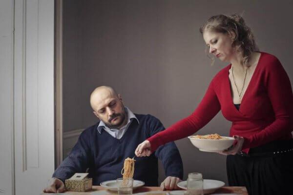 Eine Frau tischt das Essen für einen Mann auf.