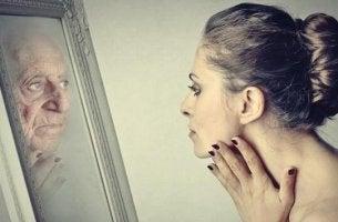 Dorian-Gray-Syndrom - junge Frau sieht sich im Spiegel als alte Frau