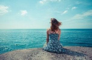 Frau sitzt am Meer