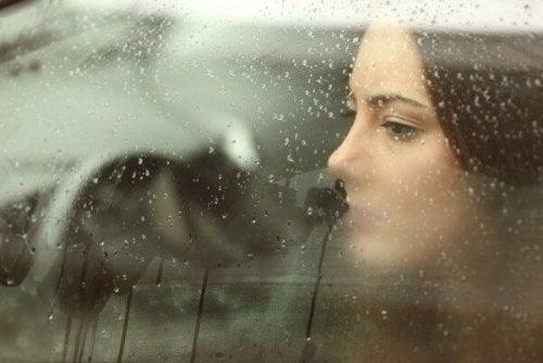 Frau sitzt nachdenklich am Fenster.