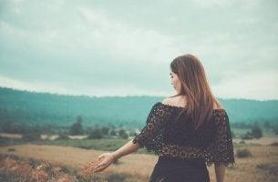 Herbst genießen - Frau spaziert durch ein Feld im Herbst