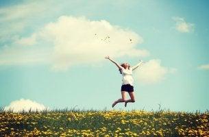 Frau springt auf einer Wiese