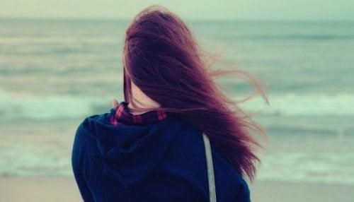 Frau steht mit Kummer am Meer
