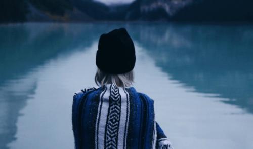 Frau steht vor einem See