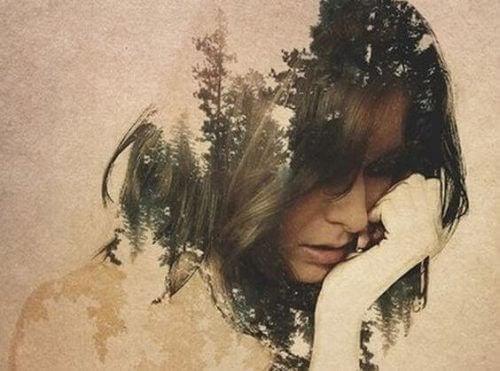 Eine traurige Frau, aus deren Kopf ein dichter Wald entsteht