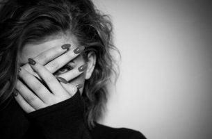 Eine Frau verdeckt aus Angst ihr Gesicht