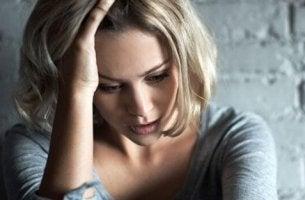 Eine verzweifelte Frau denkt über erbliche Geisteskrankheiten nach.