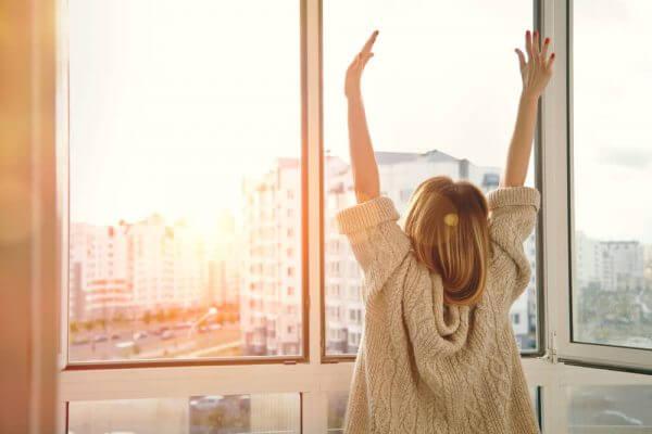 Eine Frau hat es geschafft, sie ist ausgeglichen und streckt sich im Sonnenaufgang.