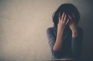 Frau lehnt an Wand und weint